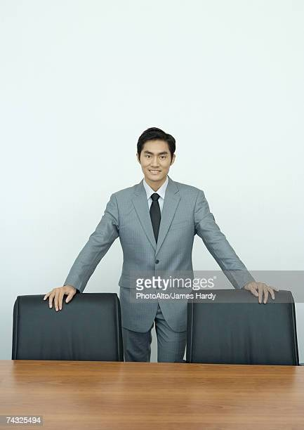 Businessman standing in conference room with hands on backs of chairs, portrait