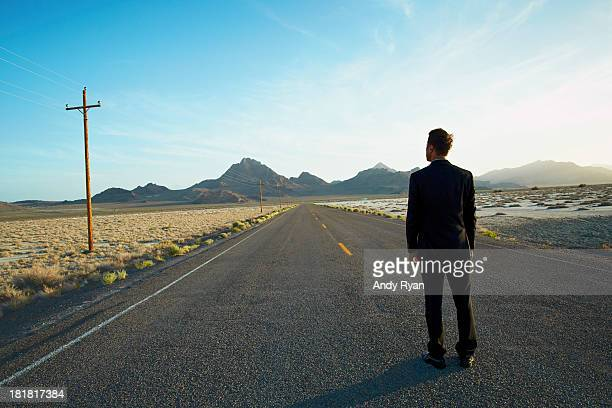 Businessman standing in desert road, looking ahead