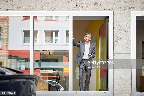 Businessman standing in door of his office, holding mobile phone