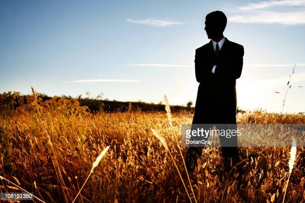 Businessman Standing in Farm Field with Arms Crossed