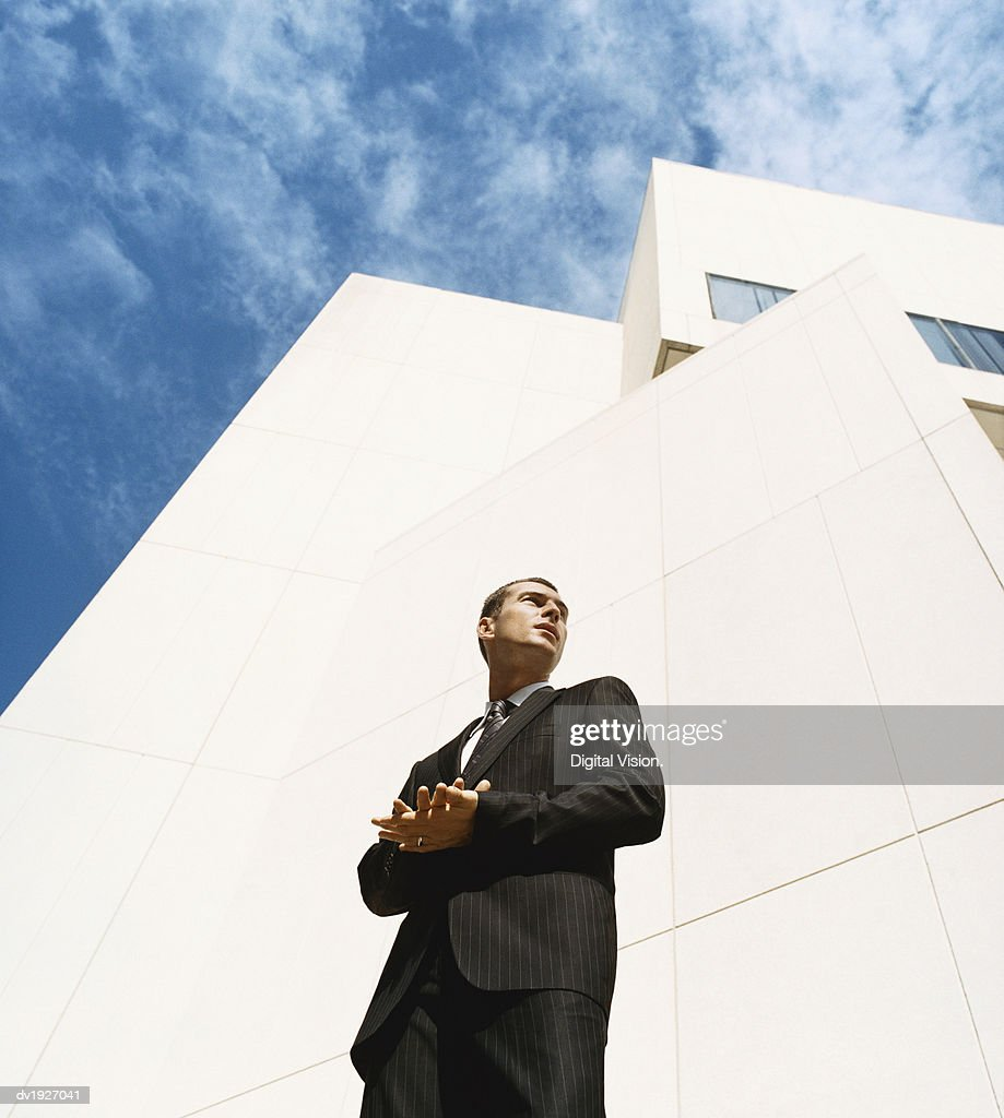 Businessman Standing in Front of an Office Building With His Hands Together : Stock Photo