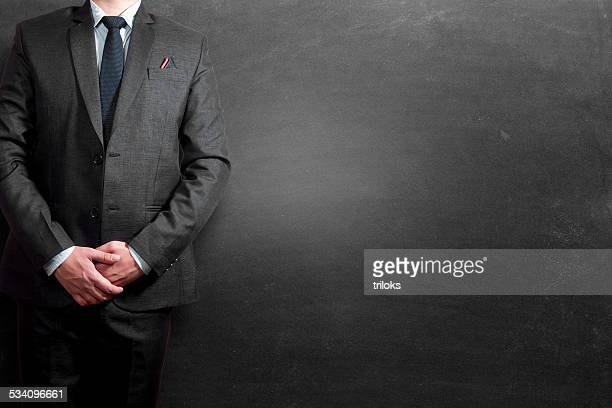Businessman standing in front of blacboard