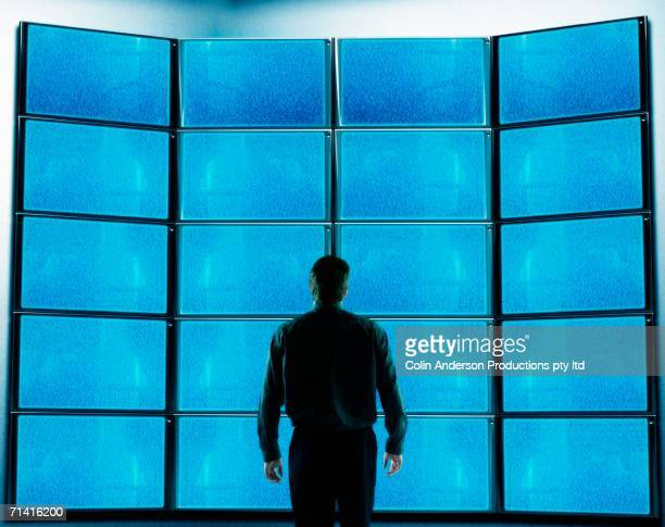 Businessman standing in front of blank television screens