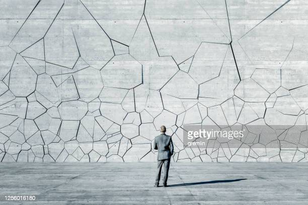 businessman standing in front of breaking wall - collapsing stock pictures, royalty-free photos & images
