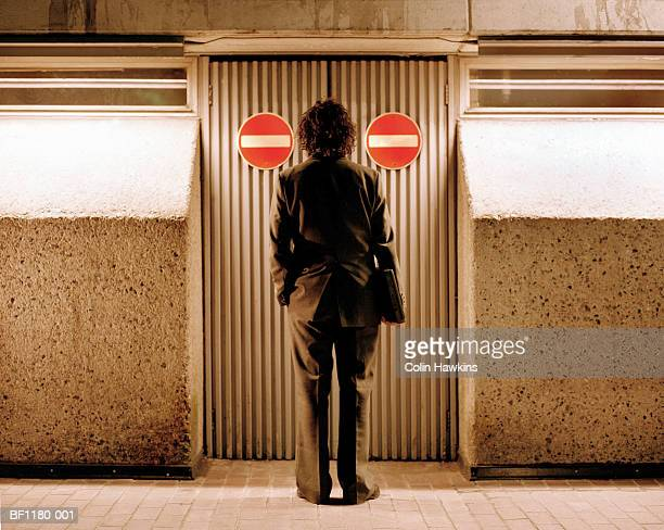 businessman standing in front of doors marked 'no entry', rear view - verboten stock-fotos und bilder
