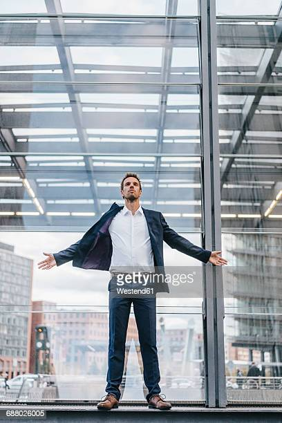 Businessman standing in front of glass pane