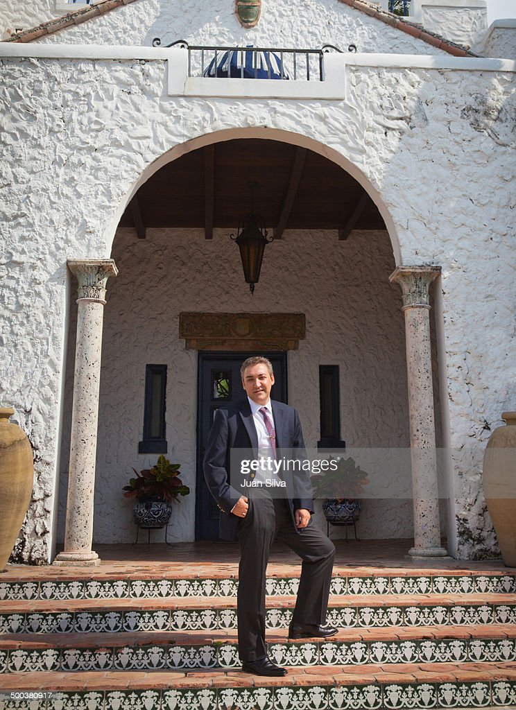 Businessman standing in front of house : Stock Photo