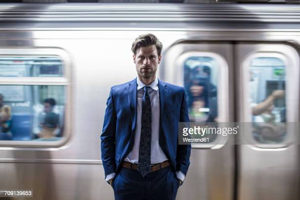 Businessman standing in front of leaving metro train