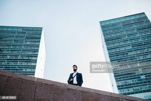 Businessman standing in front of office towers