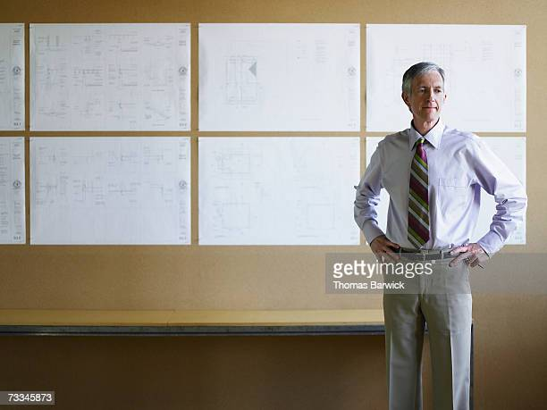 Businessman standing in front of plans on wall