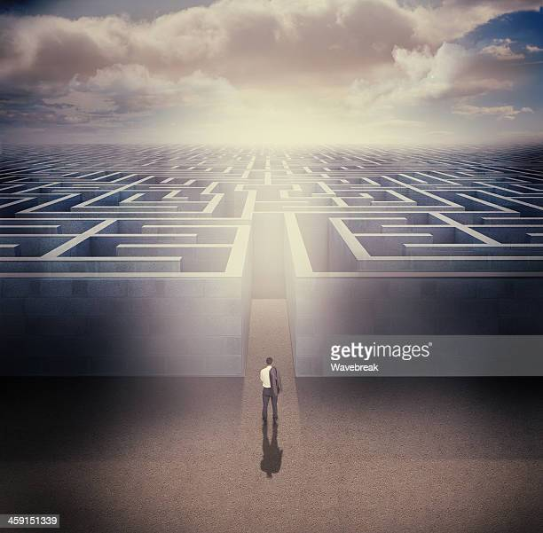 Businessman standing in front the entrance of a maze