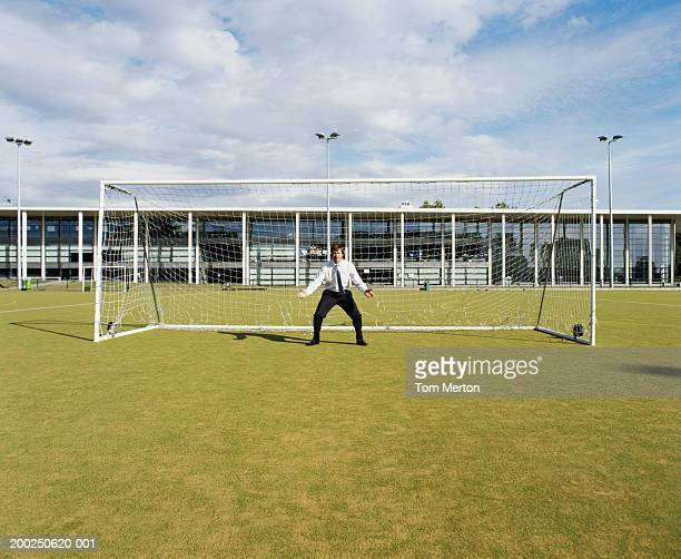 businessman standing in goal on sports field, arms outstretched - mid volwassen mannen stockfoto's en -beelden