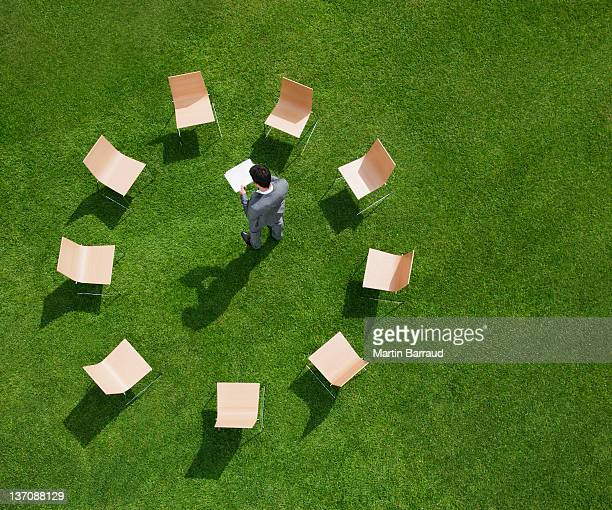 Businessman standing in grass surrounded by chairs