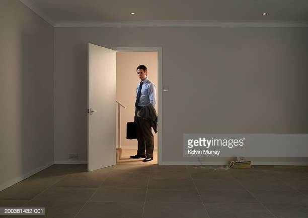 businessman standing in hall by doorway into empty room - entrata foto e immagini stock