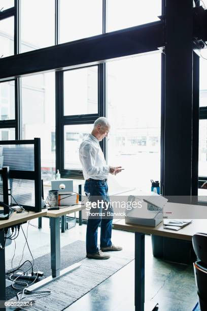 Businessman standing in high tech office working on smartphone