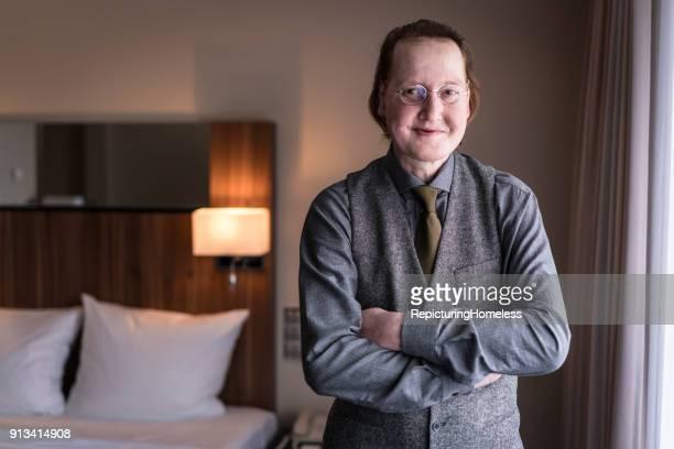 Ein Geschäftsmann steht mit verschränkten Armen in einem Hotelzimmer und schaut in die Kamera