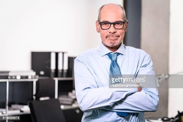 Ein Geschäftsmann sitzt auf dem Tisch und schaut zielorientiert in die Kamera
