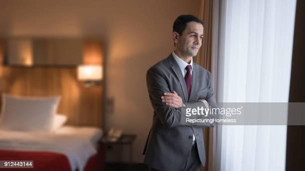 Geschäftsmann steht in Hotel und guckt aus dem Fenster