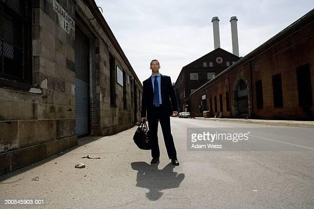 Businessman standing in industrial area