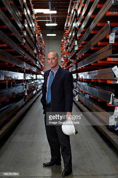 Businessman standing in metal plant