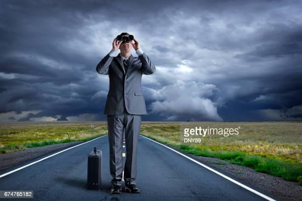 Homme d'affaires, debout au milieu de la route à la recherche par le biais de jumelles