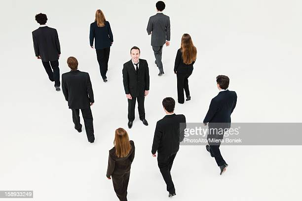 Businessman standing in midst of other anonymously dressed business professionals