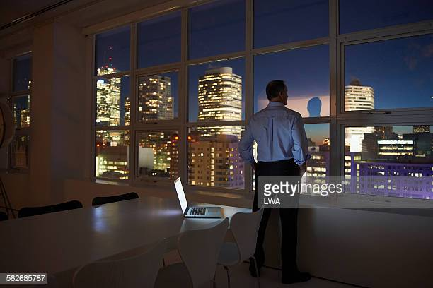Businessman standing in modern office at night
