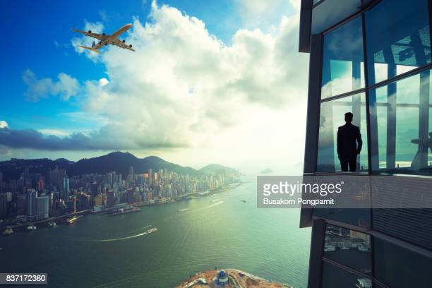 businessman standing in modern room office with looking at cityscape - wohngebäude innenansicht stock-fotos und bilder