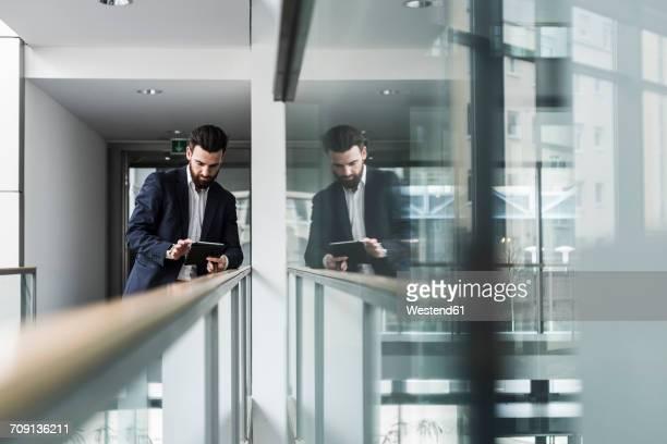 Businessman standing in office building, using digital tablet