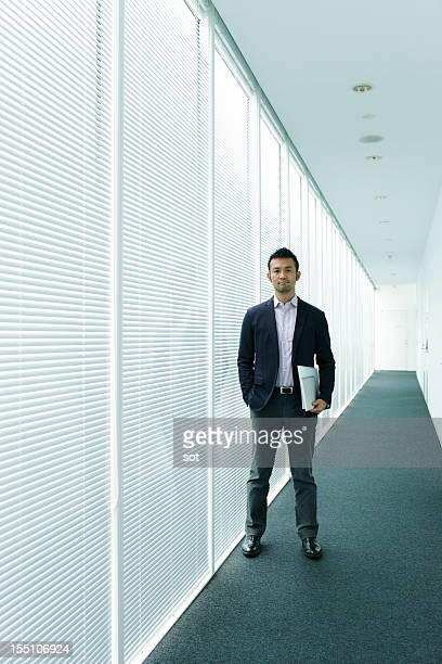Businessman standing in office hallway