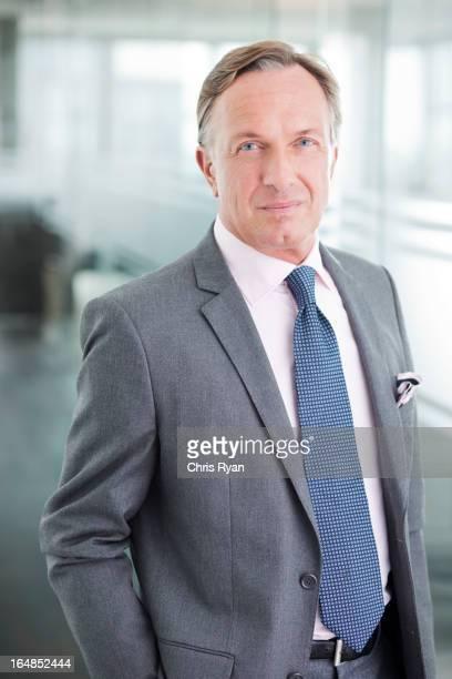Geschäftsmann, stehend im Büro-Korridor