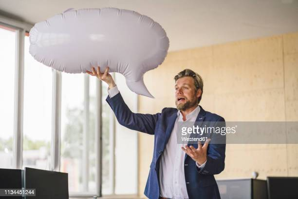 businessman standing in office, holding inflatable speech bubble - people inside bubbles stock pictures, royalty-free photos & images