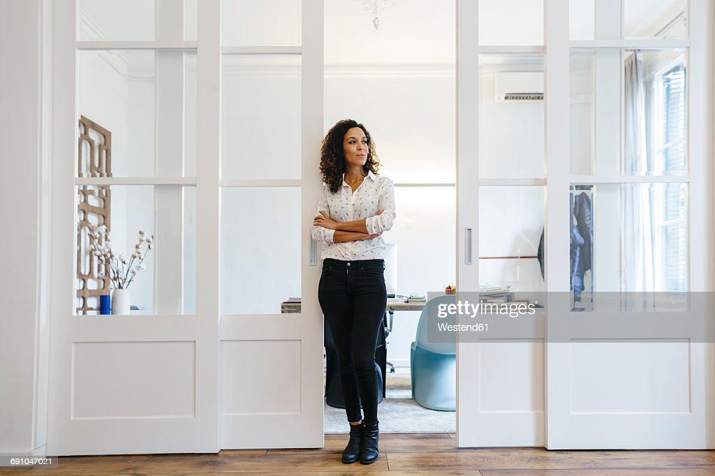 Businessman standing in office looking sideways : Stock Photo