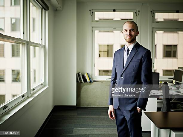 Businessman standing in office smiling