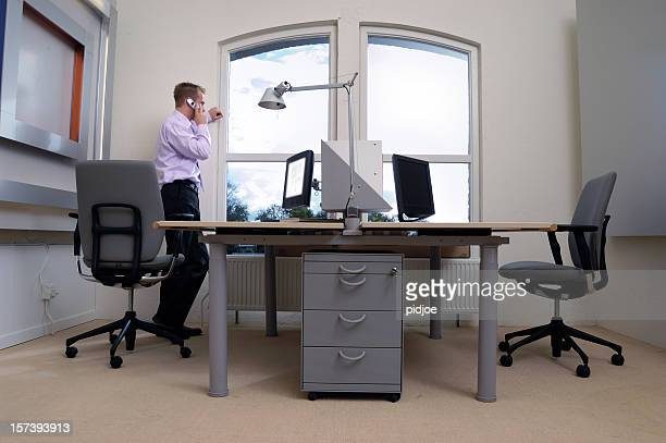 businessman standing in office talking on the phone