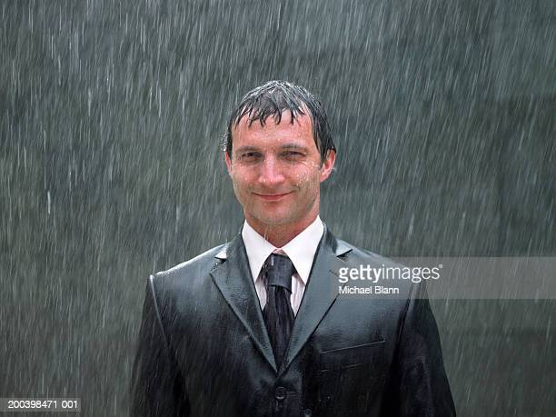 Businessman standing in rain, smiling, portrait, close-up