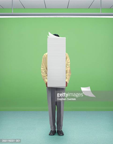Businessman standing in room, holding sack of papers