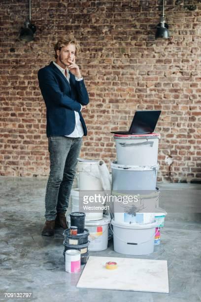 businessman standing in room with laptop and paint buckets - gründer stock-fotos und bilder