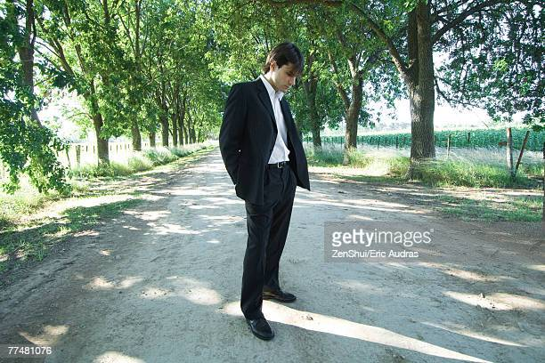 Businessman standing in rural road, looking down