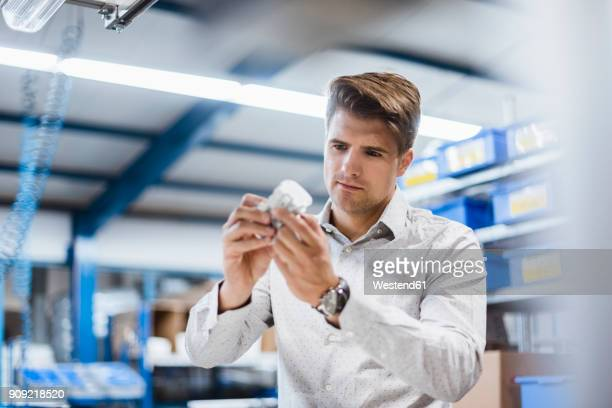 Businessman standing in shop floor, testing products