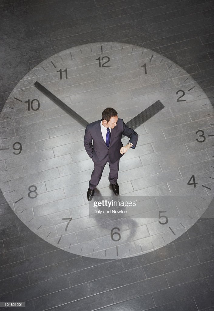 Businessman standing in standing in center of large clock and checking time on wristwatch : Stock Photo