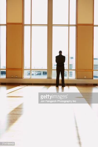 Businessman standing in sunlit room looking out window