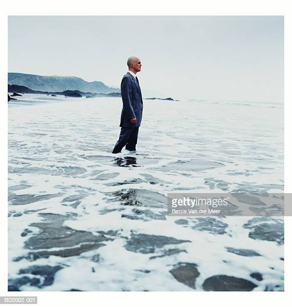 Businessman standing in surf