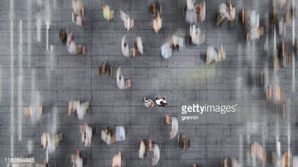 businessman standing in the fast moving crowds of commuters - immagine mossa foto e immagini stock
