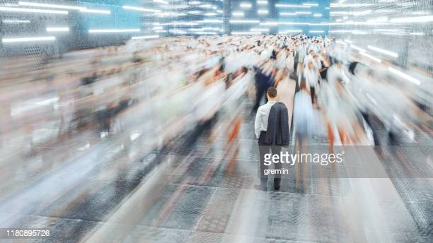 zakenman staande in de snel bewegende menigte van forenzen - tijdopname stockfoto's en -beelden