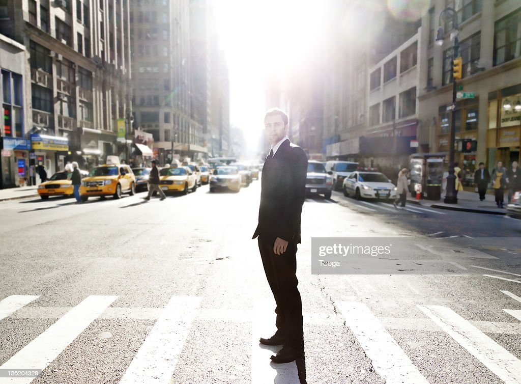 Businessman standing in the middle of busy street : Stockfoto