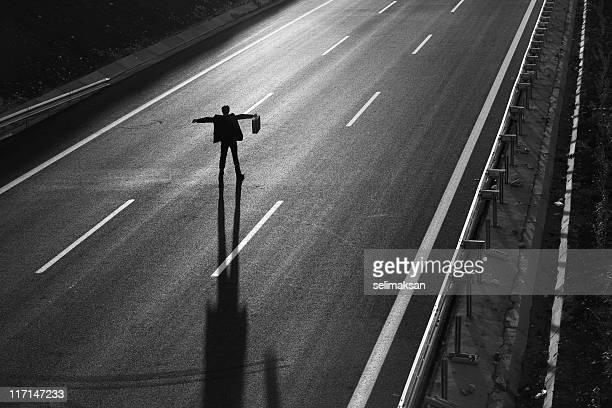 Hombre de negocios de pie en el medio de la carretera y detener el