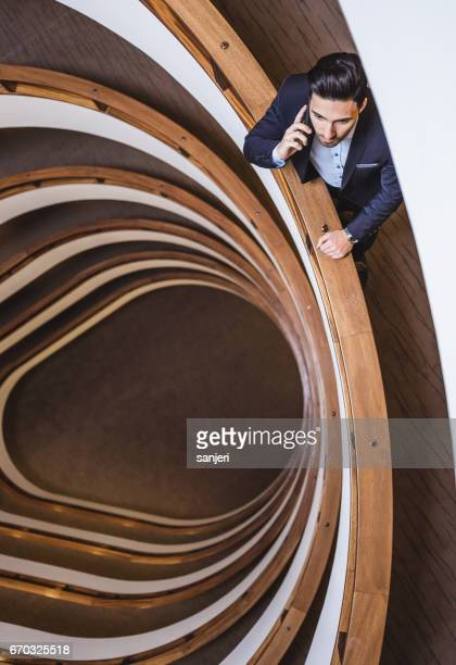 Businessman Standing in the Office Corridor Making a Call