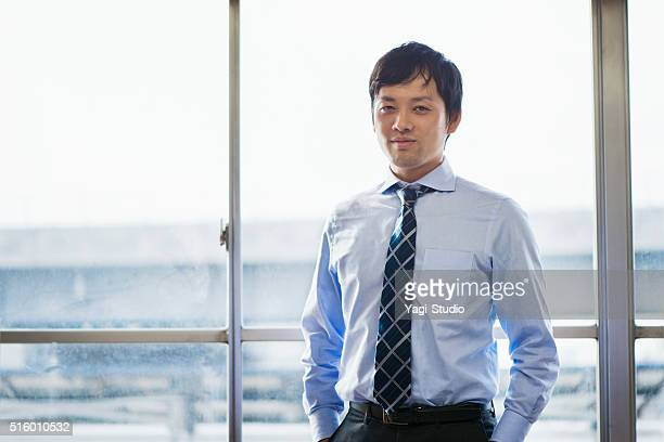 ビジネスマンに立っているオフィスのウィンドウ
