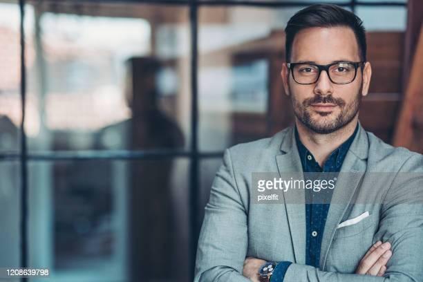 empresário em pé no escritório - confiança - fotografias e filmes do acervo